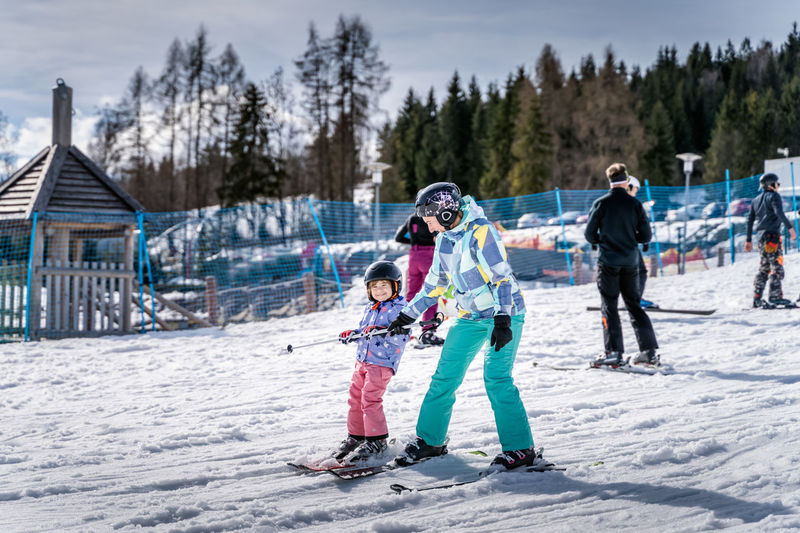 Full length of mother and daughter in snow during winter