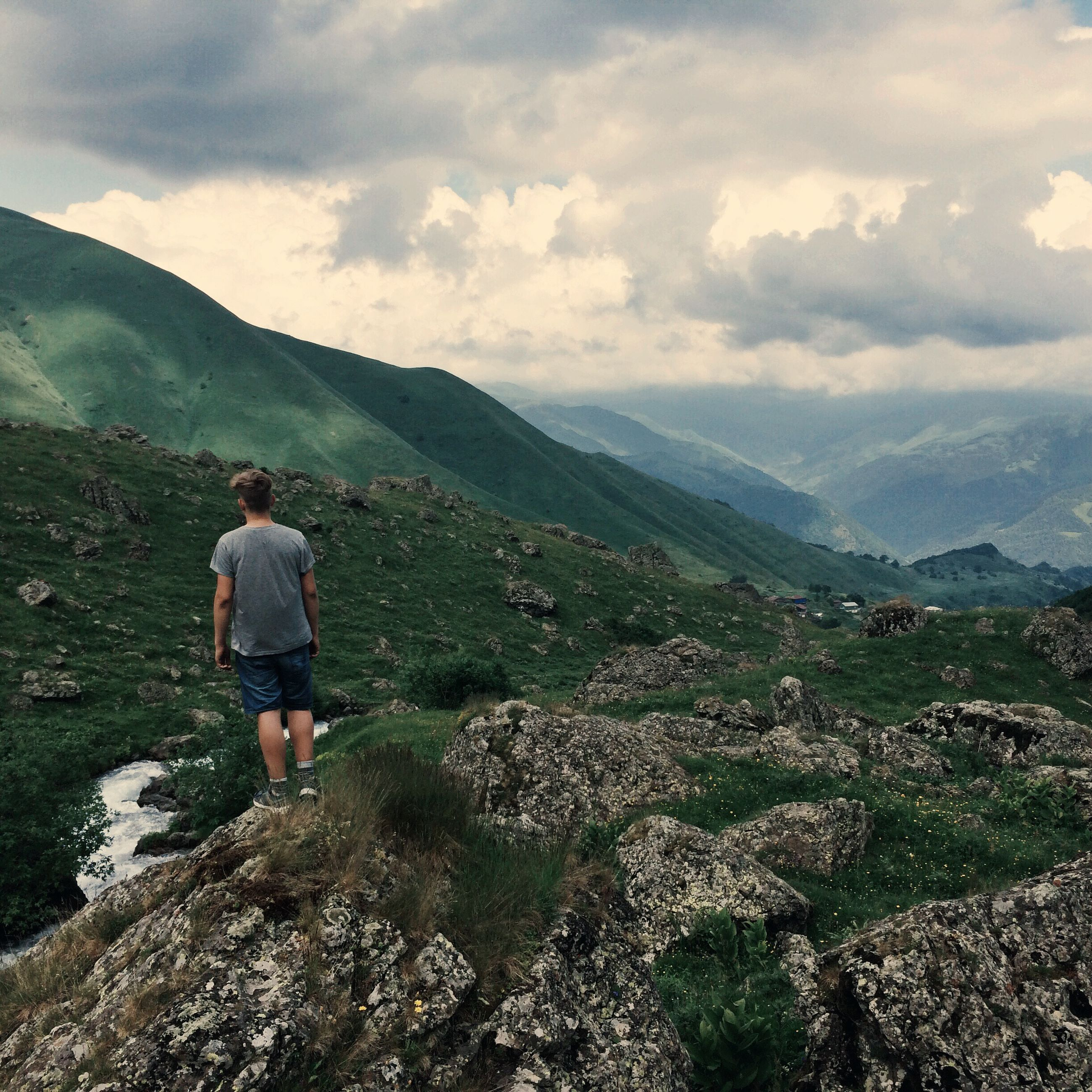 mountain, lifestyles, leisure activity, mountain range, sky, tranquility, tranquil scene, scenics, rear view, full length, beauty in nature, landscape, nature, casual clothing, rock - object, standing, cloud - sky, men