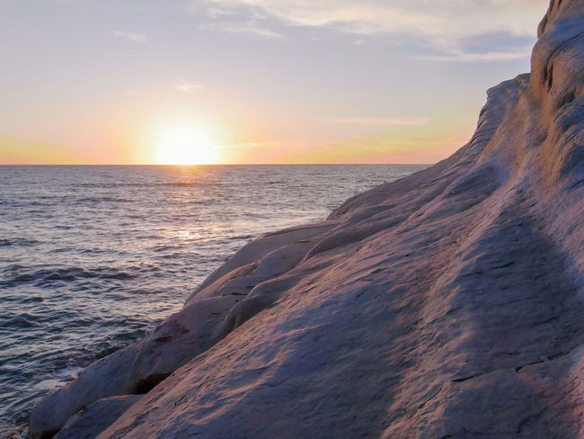 "Sunset seen from the white cliff called ""Scala dei Turchi"", near Agrigento (Sicily) Agrigento Cliff Horizon Italy Landscape Mediterranean  Nature Ocean Outdoors Realmonte Rock Scala Dei Turchi Scenics Sea Seascape Sicily Sky Sun Sunlight Sunrise Sunset Water White"