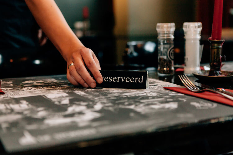 Midsection Of Woman Holding Reserved Sign At Table In Restaurant