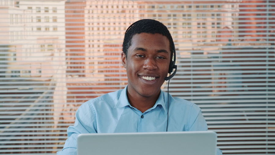Portrait of smiling young man using mobile phone
