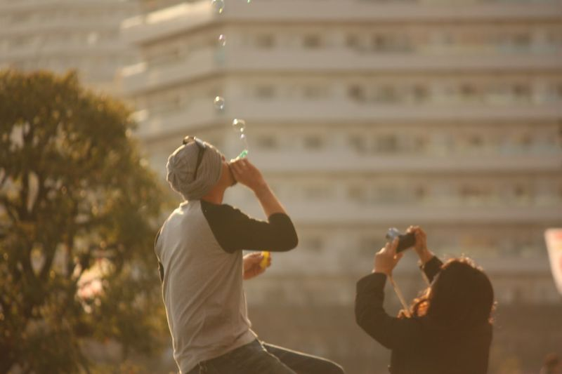 Man blowing bubbles by woman photographing against building