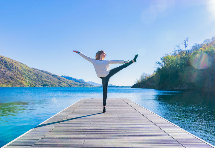 Woman Exercising With Arms Outstretched On Pier Against Lake