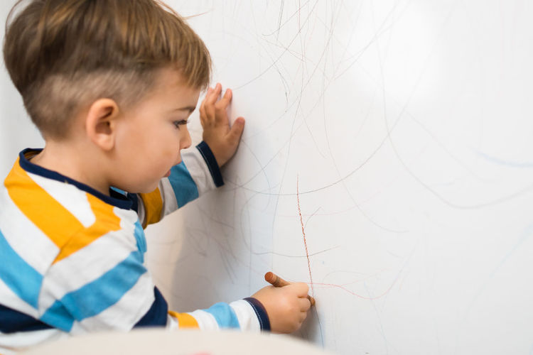 Cute Boy Drawing On Wall At Home