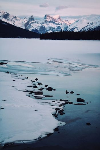 ig: emgemphoto Spring Lake Alberta Jasper National Park Maligne Lake Canada Blue Sunset Mood Thaw Ice River Jasper Canon Travel Travel Destinations Nature Beauty In Nature Water Mountain Snow Cold Temperature Winter Frozen Water Polar Climate Glacier Snowcapped Mountain Rocky Mountains Mountain Peak Mountain Range