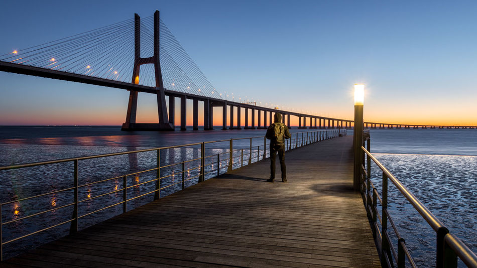 Architecture Beauty In Nature Bridge - Man Made Structure Built Structure City Clear Sky Connection Dusk Illuminated Nature Night Outdoors Railing Scenics Sea Sky Sunset Suspension Bridge Tourism Tranquil Scene Transportation Travel Travel Destinations Water Women
