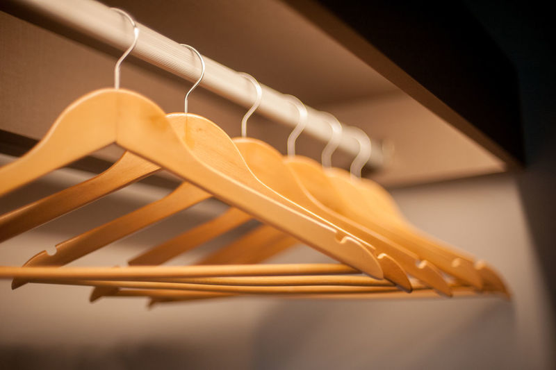 Close-Up Of Wooden Coathangers Hanging On Clothes Rack