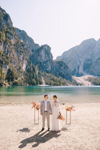Bridegroom standing on lakeshore against clear sky