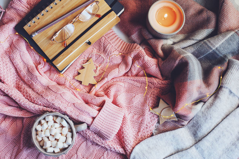 cozy winter or Christmas table with seasonal fashion clothes, hot cocoa and candles. Hygge concept Indoors  Still Life Textile No People Bed Food And Drink Blanket Day Pink Color Table Clothing Winter Wintertime Cozy Cozy At Home Hygge Cocoa Book Candle Warm Clothing Glasses Reading Notes