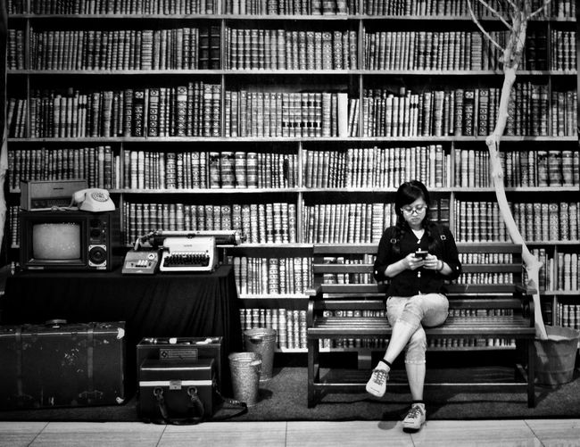 Woman using mobile phone while sitting on bench against bookshelf