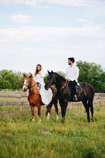 Couple riding horse on field
