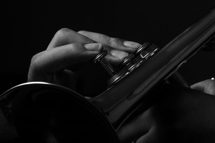 Cropped hand playing trumpet against black background