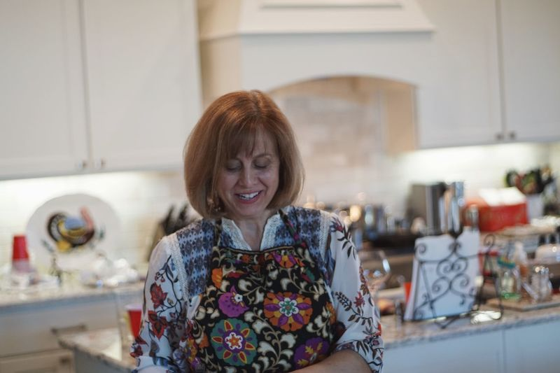 Smiling mid adult woman working in kitchen at home