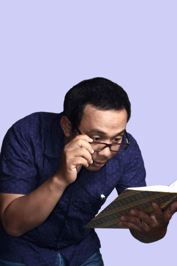 Asian man having trouble with eyesight while reading a book Adult Concentration Day Eyeglasses  Front View Holding Human Hand Indoors  One Person People Real People Studio Shot Technology Weapon Young Adult