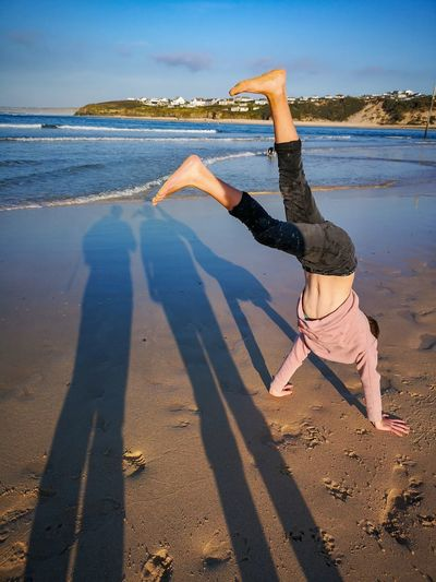 prefers to be upside down Shadows Cornwalls Coastline Shadows Of Two People And A Boy Doing A Handstand On The Beach Autumn Evenings Porthkidney Beach EyeEm Gallery Sea Blue Sky Ways Of Seeing Children Fun Family Time Weekend Leisure My Boy