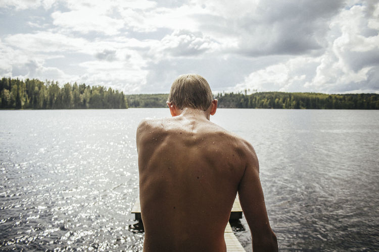 Rear view of shirtless boy standing by lake