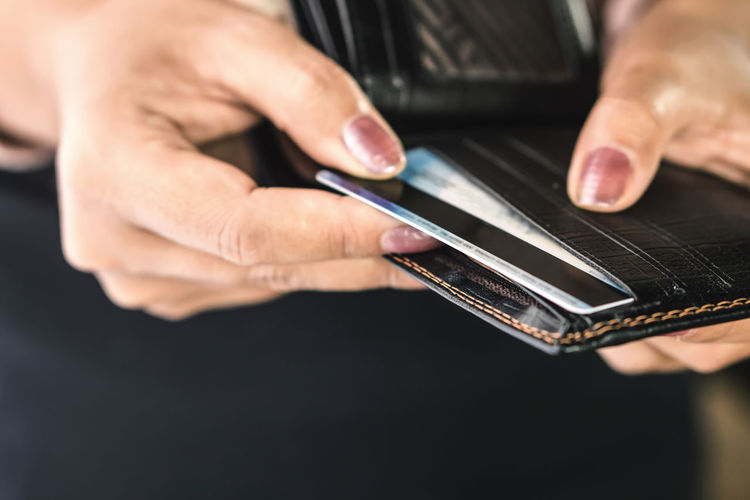 Close-up of woman inserting credit card in wallet