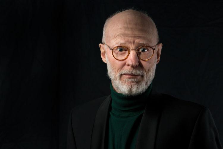 Portrait Of Senior Man Wearing Eyeglasses Against Black Background