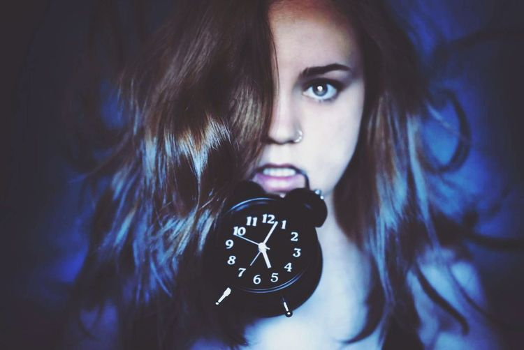 Close-up portrait of young woman carrying alarm clock in mouth