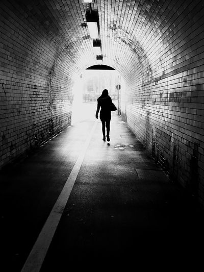 Rear View Full Length Of Woman Walking In Tunnel