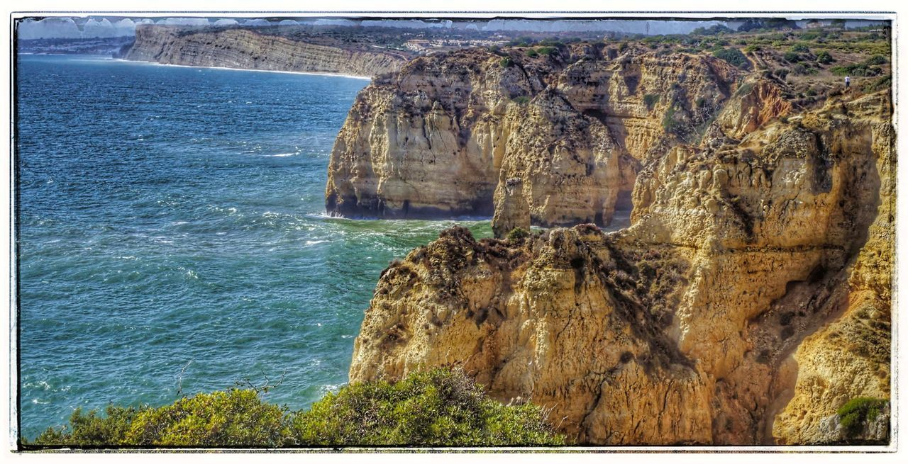 PANORAMIC VIEW OF ROCK FORMATION ON SEA
