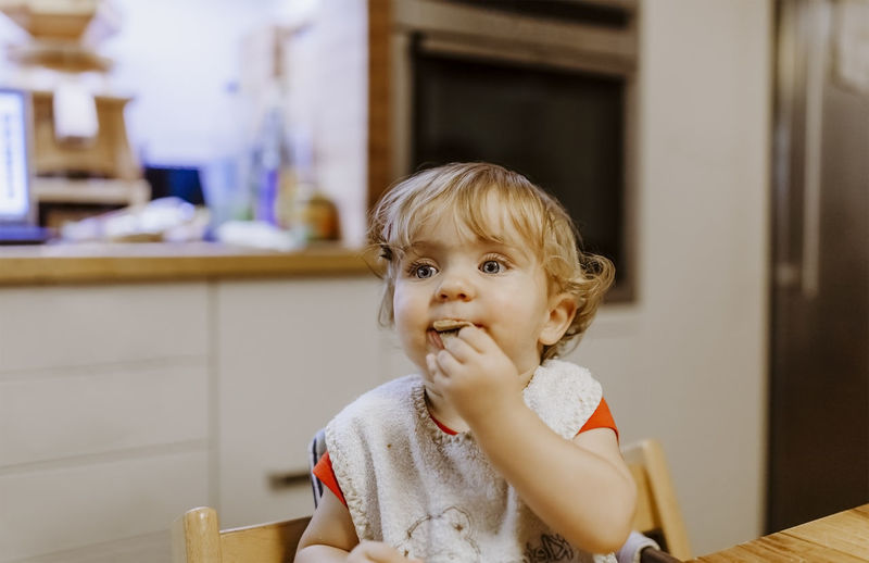 Portrait Of Cute Girl Eating Food On Table At Home