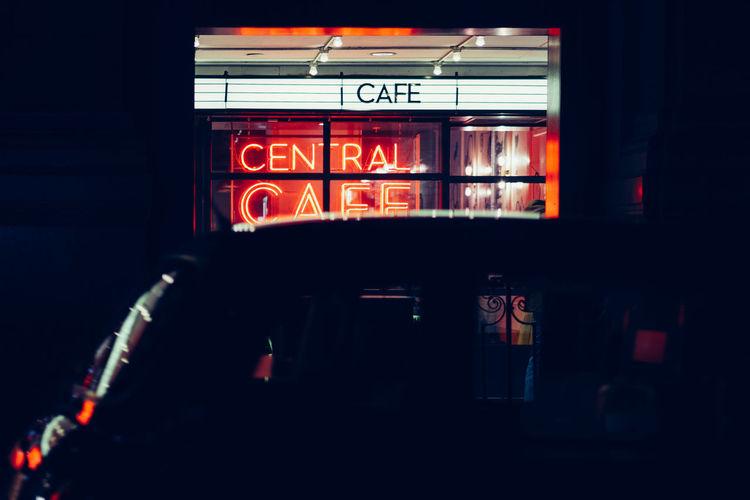 Illuminated text on store at night