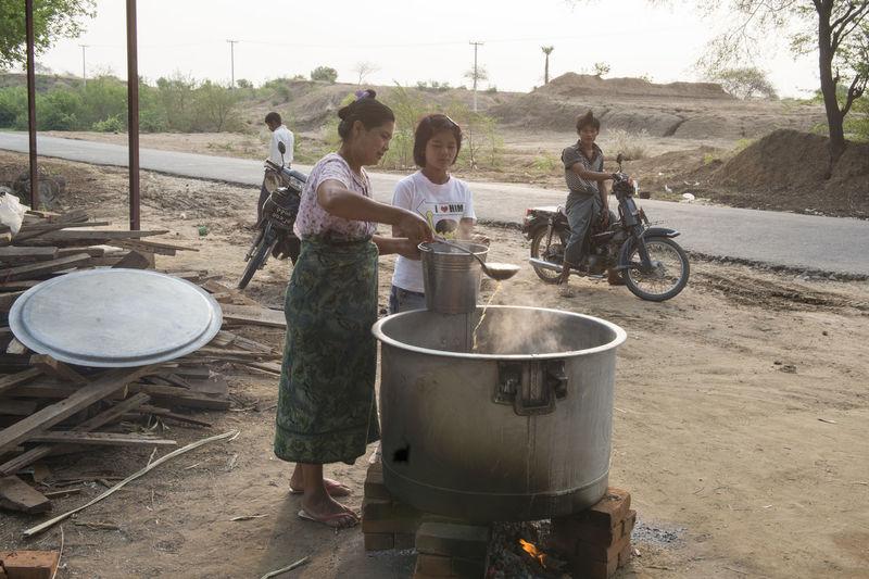 Girl looking at woman preparing food outdoors