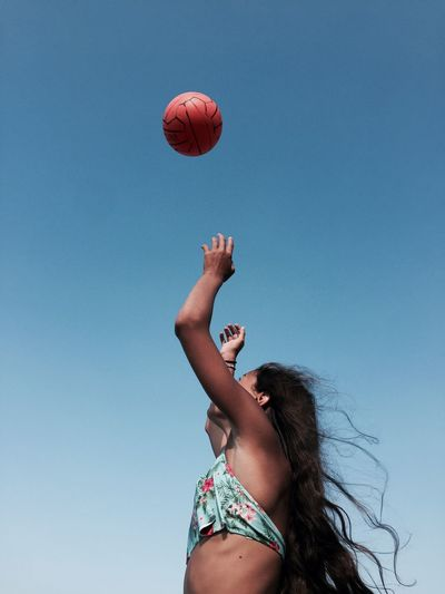 Low angle view of young woman playing clear sky