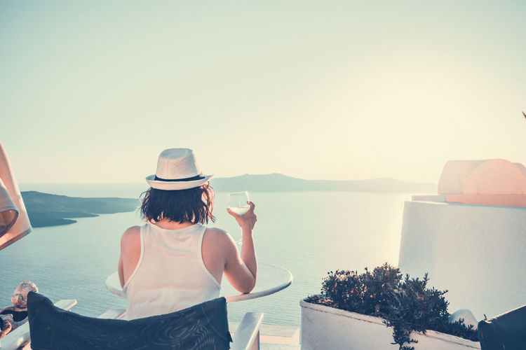 Fine Wine Deck Chair Adult Beauty In Nature Clear Sky Copy Space Female Hat Horizon Over Water Leisure Activity Lifestyles Looking At View Nature One Person Outdoors Real People Rear View Santorini Scenics - Nature Sea Sky Sunset Waist Up Water Wineglass Women