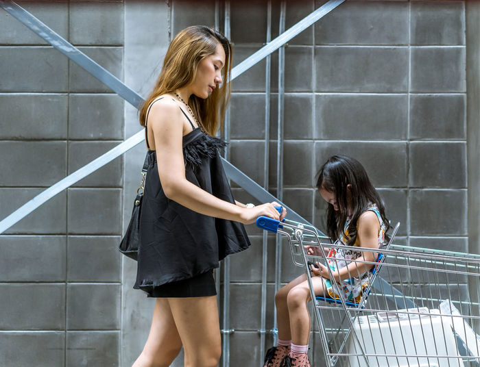Mom Places daughter In Shopping Cart Young Adult Young Women Women Real People Lifestyles Two People Architecture Standing Casual Clothing Adult Holding Bag Railing People Leisure Activity Staircase Fashion Three Quarter Length Built Structure Beautiful Woman Consumerism Hairstyle