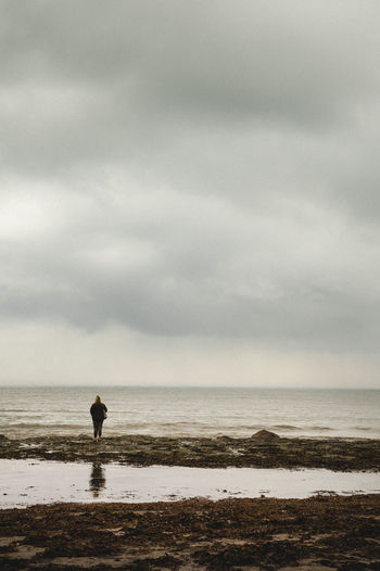 Rear View Of Woman At Calm Sea Against Sky