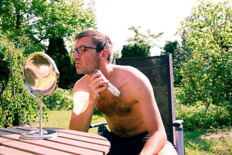 Shirtless man trimming beard in yard