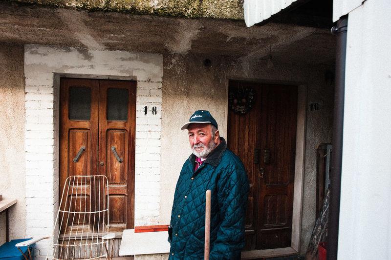 Portrait of smiling man standing against building