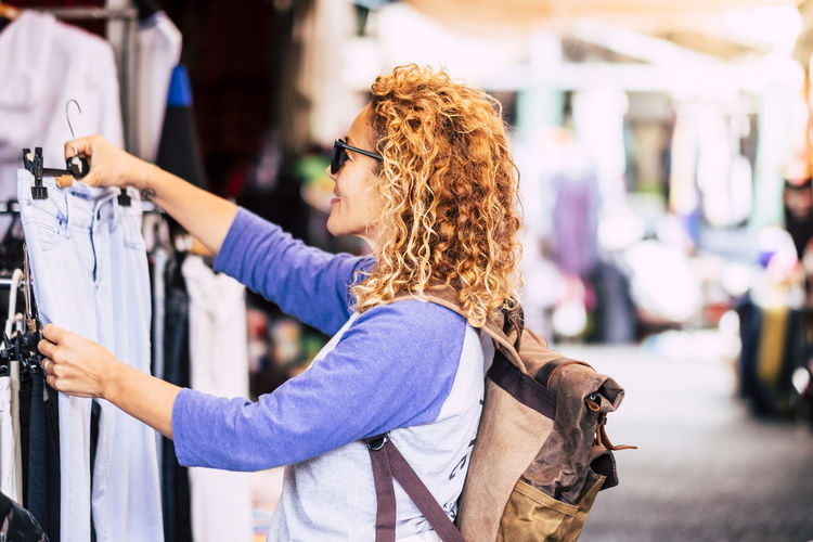 Cheerful traveler young blonde curly woman looking and choosing clothes at the used market during alternative vacation - shopping lifestyle concept for nice people Focus On Foreground Women One Person Lifestyles Real People City Leisure Activity Hairstyle Side View Adult Street Hair Curly Hair Day Waist Up Architecture Casual Clothing Beautiful Woman Shopping Store Market Caucasian Enjoyment Backpack Backgrounds Choosing Clothes Vacations Cheerful Young Adult Female Outdoors Consumerism Business
