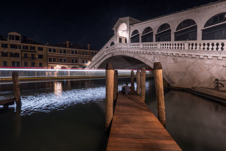 View of bridge over canal at night