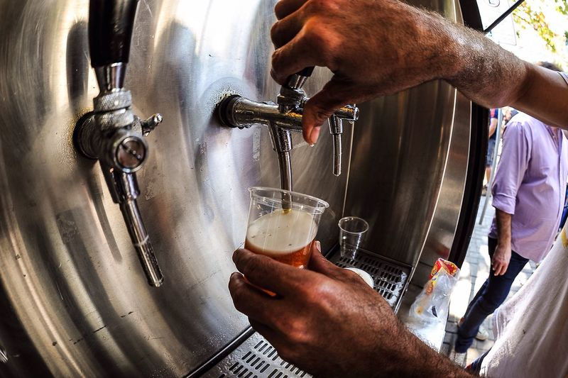 Man pouring beer in disposable glass from tap
