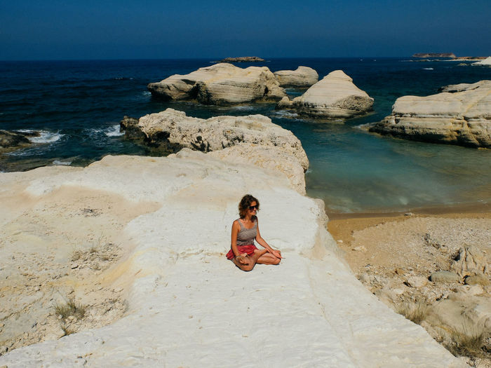 Young woman practicing yoga while sitting on rock formation at beach