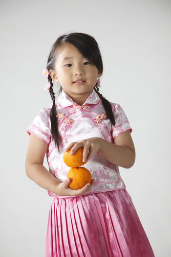 Cute Girl Holding Oranges Against White Background
