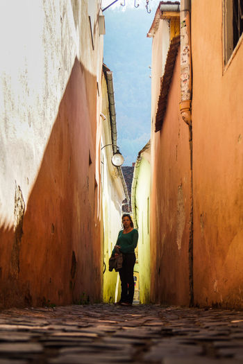 Surface level image of mid adult woman standing on alley amidst buildings in city