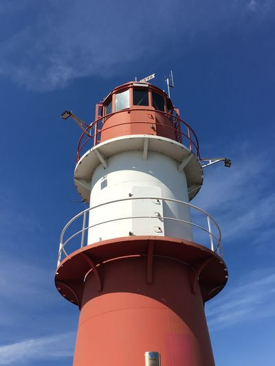 Low angle view of lighthouse against blue sky - warnemünde germany
