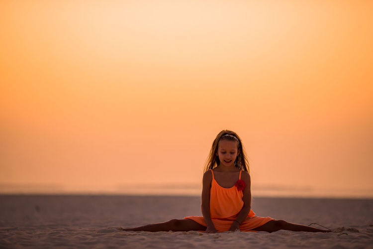 Smiling girl sitting on beach against clear sky during sunset