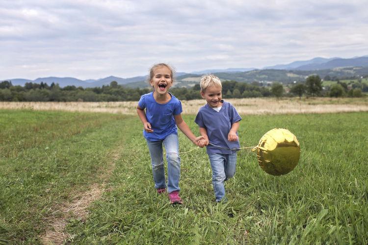 Full length of smiling boy on grassy field