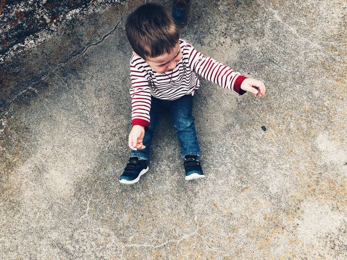 High angle view of boy crying while sitting on footpath