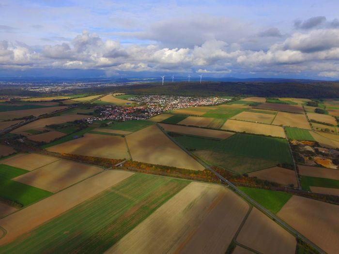 Aerial View Of Agricultural Landscape Against Cloudy Sky