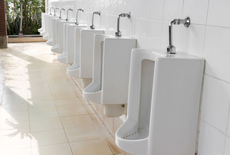 White Urinals On Tiled Wall