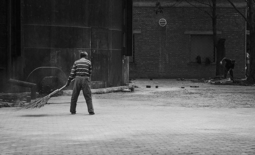 Full length rear view of sweeper cleaning street against building
