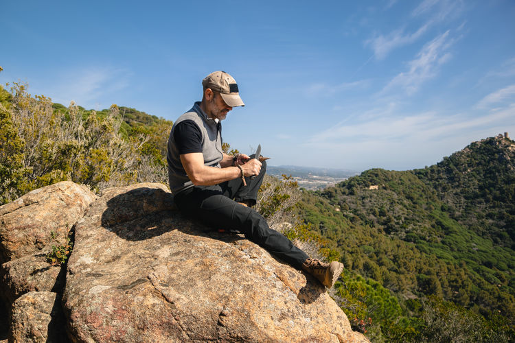 Full length of young man sitting on rock