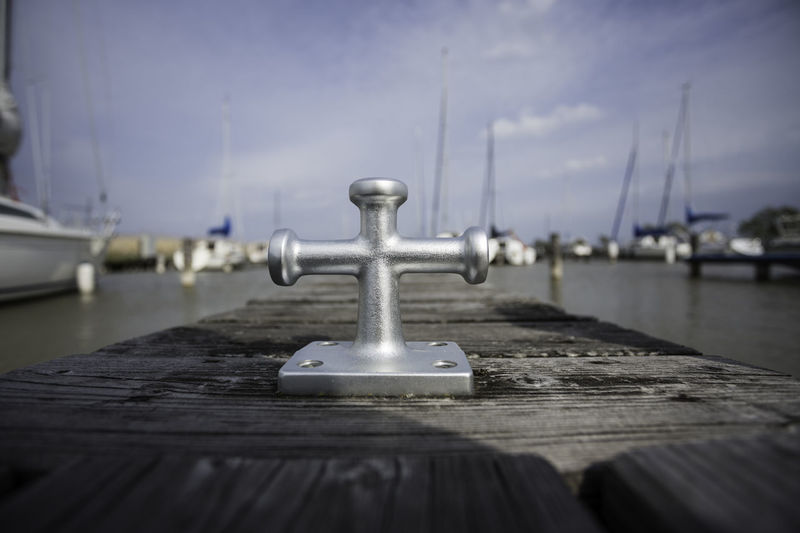 Close-up of bollard on pier over sea