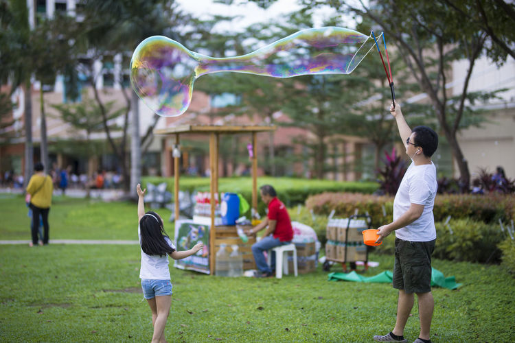 Strolling around. New Year's Day. Focus On Foreground Real People Lifestyles Eyeem Philippines The Week on EyeEm Playing Men Childhood Leisure Activity Child Park Boys Males  Park - Man Made Space Day Incidental People Fun Group Of People Girls Enjoyment Bubble Wand Bubble Outdoors
